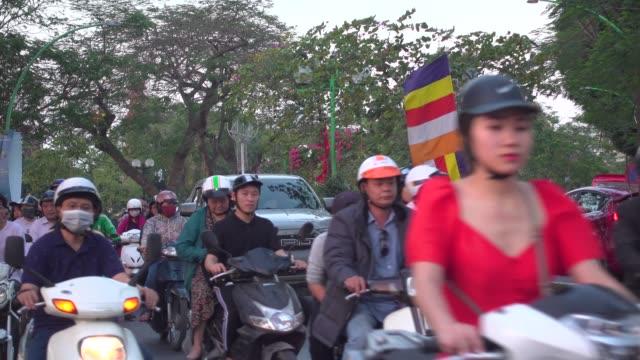 hanoi street full of motorcycles. thanh nien road. vietnam b-roll with buddhist flag - 大気汚染点の映像素材/bロール
