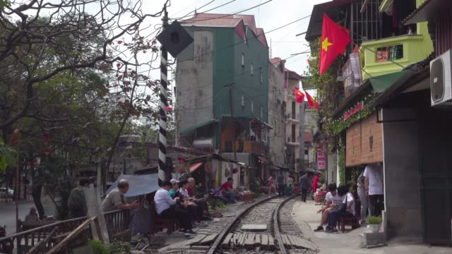 hanoi train street. famous place with tourists. iconic image of narrow street with the railway in the middle of the buildings - bahngleis stock-videos und b-roll-filmmaterial
