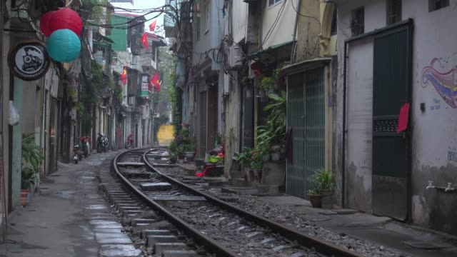 hanoi train street. iconic image of narrow street with the railway in the middle of the buildings - newly industrialized country stock videos and b-roll footage