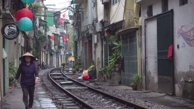 hanoi train street. iconic image with woman dressing conical hat walking along narrow street with the railway in the middle of the buildings - bahngleis stock-videos und b-roll-filmmaterial