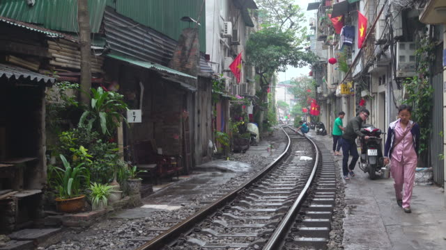 hanoi train street lifestyle. iconic image of narrow street with the railway in the middle of the buildings - routine stock videos & royalty-free footage
