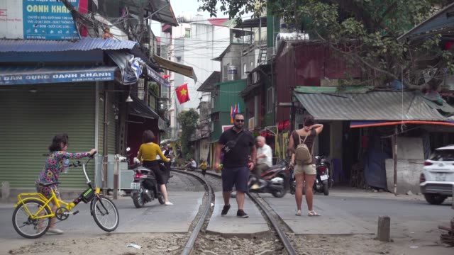 hanoi train street. touristic spot. iconic image of narrow street with the railway in the middle of the buildings - railway track stock videos & royalty-free footage