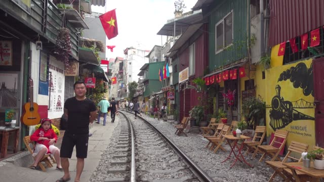 Hanoi Train street. Touristic spot with cafe and national Vietnamese flag. Iconic image of narrow street with the railway in the middle of the buildings