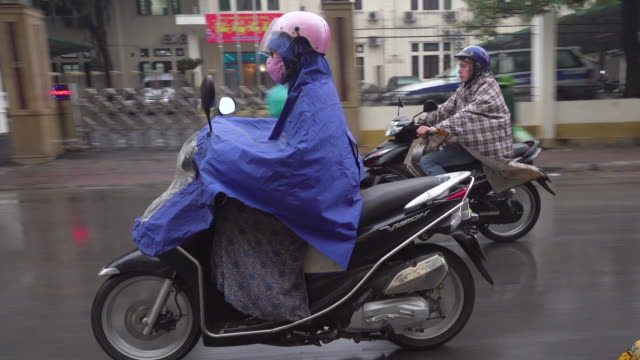 hanoi vietnam on a rainy day. people con a motorbike. taxi point of view - communism stock videos & royalty-free footage