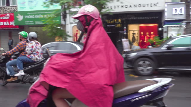 vídeos de stock, filmes e b-roll de hanoi vietnam on a rainy day. woman on a motorbike with pink raincoat. taxi point of view - rosa cor