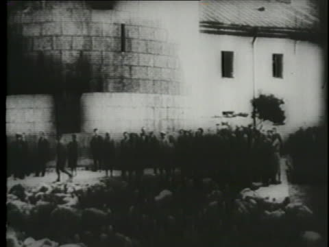 hans frank testifies at the nuremberg trials with images of dead holocaust victims amid burnt out buildings. - genocide stock videos & royalty-free footage