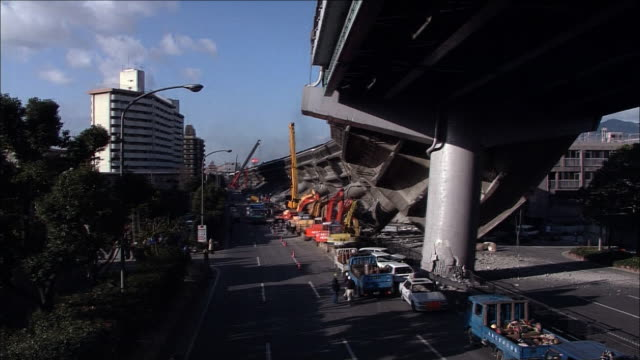 hanshin expressway toppled over sideways due to collapsed bridge girders of a viaduct. wide shot. zoom in. fallen bridge girders and mobile cranes... - lying on side stock videos & royalty-free footage