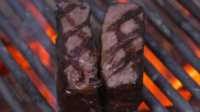 hanwoo (korean native cattle) sirloin steak being broiled on grill rack - grigliare video stock e b–roll