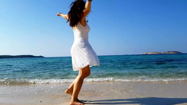 vídeos de stock e filmes b-roll de happily spinning by the sea - vestido branco