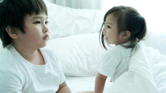 happiness cute asian girl with boring brother while talking in the bedroom - babies in a row stock videos & royalty-free footage