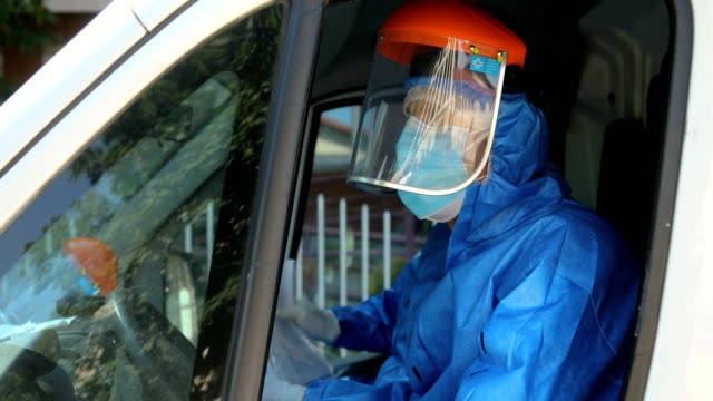 happiness driver in a blue protective medical suit with white gloves enters the ambulance - human arm stock videos & royalty-free footage