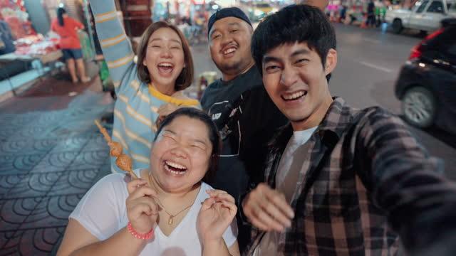 vídeos y material grabado en eventos de stock de grupo de felicidad de amigos disfrutando en el día de trucos y selfie con la comida. - puesto de mercado