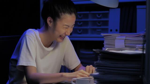 vídeos y material grabado en eventos de stock de felicidad de las jóvenes asiáticas de 28 años vendida a videoconferencia durante la ubicación remota por computadora en casa por la noche de trabajar hasta tarde. covid-19 trabajando desde el concepto de hogar. - estudio habitación