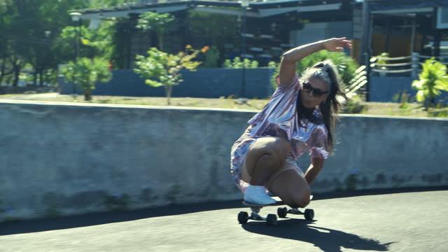 glück der älteren sportlichen frau lateinamerikanischer und hispanischer ethnizität mit sonnenbrille und grauhaarigem alter von 53 jahren, die an einem sonnigen tag skateboard spielen. senioren im sportkonzept. - latin american and hispanic ethnicity stock-videos und b-roll-filmmaterial