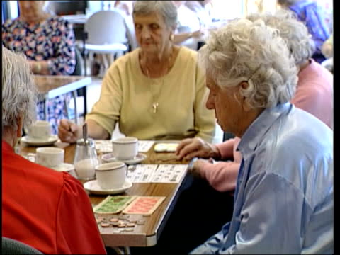vídeos y material grabado en eventos de stock de survey reveals wealth required for happiness lib elderly women sitting playing bingo - bingo