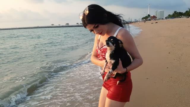 stockvideo's en b-roll-footage met geluk vrouw en een mooie hond met goede tijd op het strand bij zonsondergang samen - genomen met mobiel apparaat