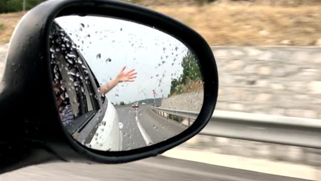 Felicidad - mujer joven en un coche, mano en el aire