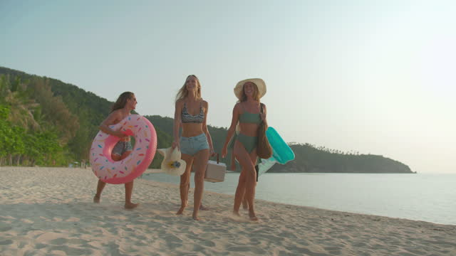 happpiness to group of young multi-ethnic five people of friends having fun while walk and helping each other while carrying a rubber ring, plastic cooler with fun of sunset on sand beach summer holiday vacation together. travel concept - hawaii islands stock videos & royalty-free footage