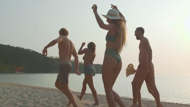 happpy zu gruppe von jungen multi-ethnischen fünf menschen von freunden, die spaß daran haben, vor dem schönen meer am strand sonnenuntergang tag zusammen zu gehen. happiness in nature konzept. - beach holiday stock-videos und b-roll-filmmaterial