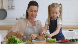 Happy 30s woman teaching small daughter preparing healthy vegan food.