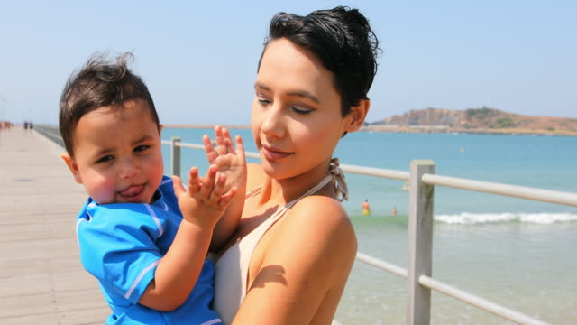 happy aboriginal australian mother and son at the beach - australian aboriginal culture stock videos and b-roll footage