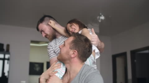 stockvideo's en b-roll-footage met happy adopted girl having fun with gay parents - twee ouders