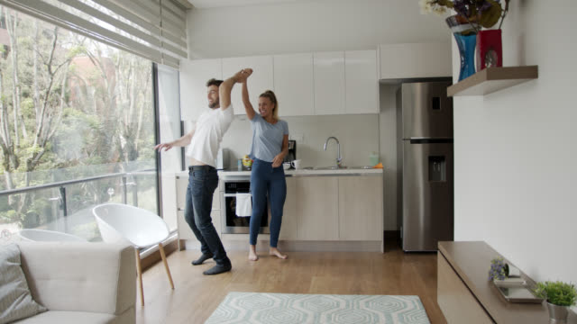vídeos de stock e filmes b-roll de happy adult couple at home having fun dancing and smiling - descalço