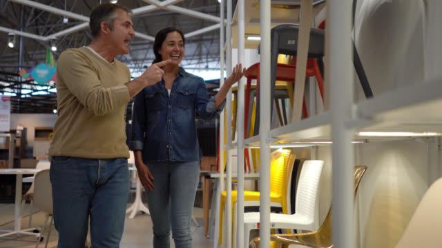 glückliches erwachsenes paar auf der suche nach einem stuhl in einem möbelhaus diskutieren sehr fröhlich beim betrachten auf display - möbel stock-videos und b-roll-filmmaterial