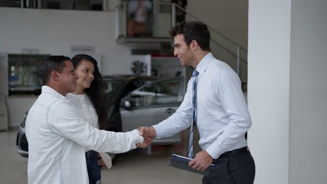 vídeos de stock, filmes e b-roll de casal adulto feliz recebendo as chaves de seu novo carro de vendedor amigável em uma concessionária de carros - vender