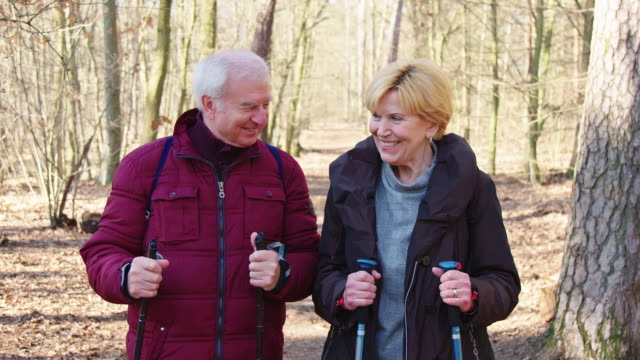 happy affectionate couple with hiking poles - stagione video stock e b–roll