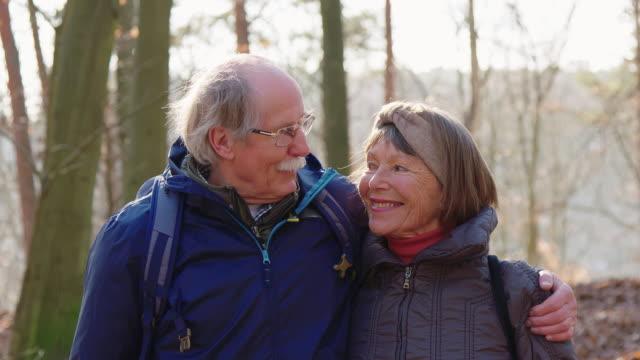 vídeos de stock e filmes b-roll de happy affectionate elderly couple in forest - exploration