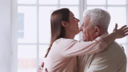 Happy affectionate young adult granddaughter visit hug senior grandfather