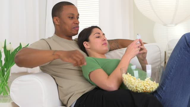 happy african american and caucasian couple using smart phone and eating popcorn - dreiviertelansicht stock-videos und b-roll-filmmaterial