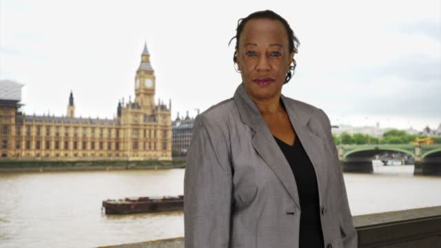 happy african american businesswoman poses for portrait near big ben - big ben点の映像素材/bロール