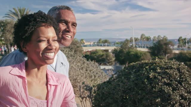 happy african american couple embrace on beach boardwalk - boardwalk stock videos & royalty-free footage
