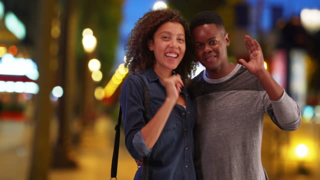 happy african american couple on the champs-elysees smile and wave at camera - guy waving stock videos & royalty-free footage