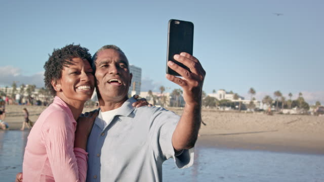 happy african american couple take selfie on beach - active seniors stock videos & royalty-free footage