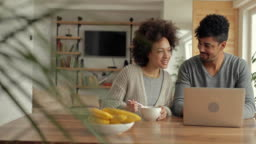 Happy African American couple using laptop and having fun while watching something funny on the Internet.