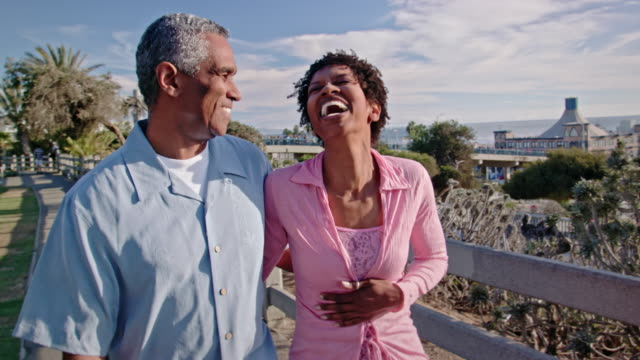happy african american couple walk boardwalk - mature couple stock videos & royalty-free footage