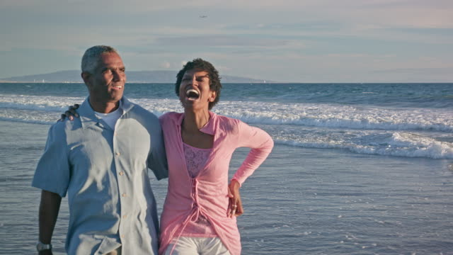 happy african american couple walk on the beach - mature adult stock videos & royalty-free footage