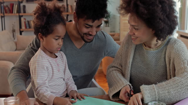 vídeos de stock e filmes b-roll de happy african american family having fun while making something creative with paper and scissors. - grupo pequeno de pessoas
