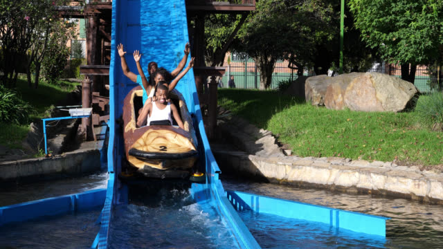 happy african american family on a log ride at an amusement park having fun - acquascivolo video stock e b–roll