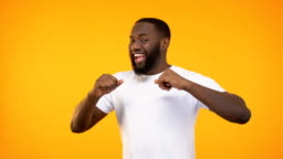 Happy african american man dancing and singing, isolated on yellow background