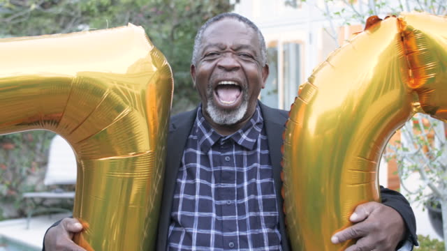 happy african american man holds birthday balloons, close up - black jacket stock videos & royalty-free footage