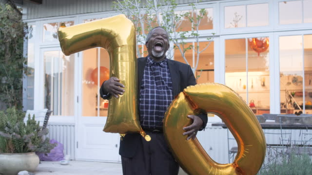 happy african american man holds birthday balloons, medium shot - 10 sekunden oder länger stock-videos und b-roll-filmmaterial