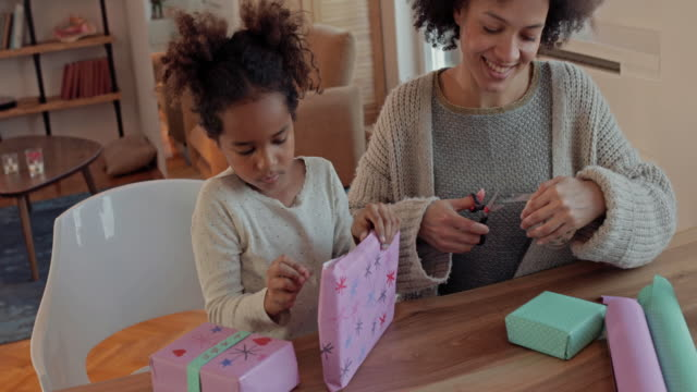 happy african american mother and daughter wrapping presents together at home. - wrapping paper stock videos & royalty-free footage