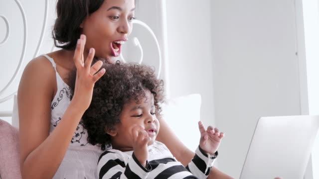 vídeos de stock, filmes e b-roll de feliz africano mãe americana e miúdo que usa o portátil para prestar atenção, desenhos animados de canto que têm o divertimento. passar tempo com seu bebê bonito em casa. família, inovação, estilo de vida, tecnologia e conceito de maternidade. pe - quarto de dormir