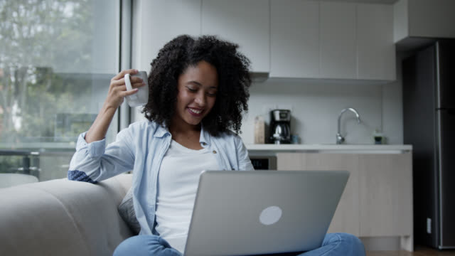 happy african american woman at home relaxing on couch enjoying a tea while chatting using laptop - mixed race person stock videos & royalty-free footage
