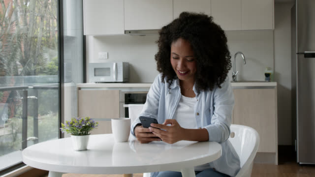 happy african american woman at home using app on her smart phone and drinking a cup of coffee - text messaging stock videos & royalty-free footage