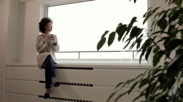 happy african american woman relaxing by the window during her coffee time. - resting stock videos & royalty-free footage